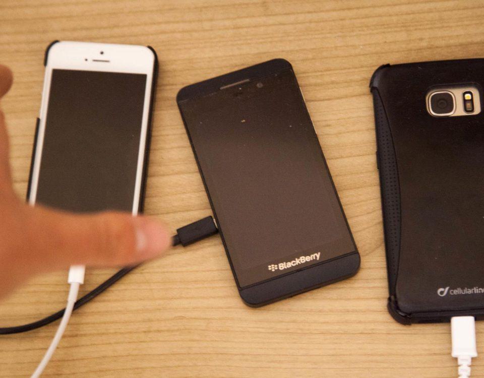 Symbolfoto von drei Handys während eines Ladevorgangs mit einer Hand, die sich danach ausstreckt.