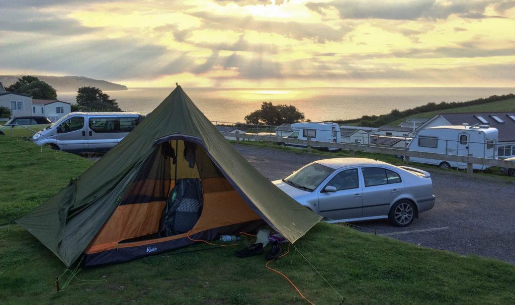 Ein Zelt steht auf einem Campingplatz. Im Hintergrund erkennt man den Sonnenuntergang über dem Meer.