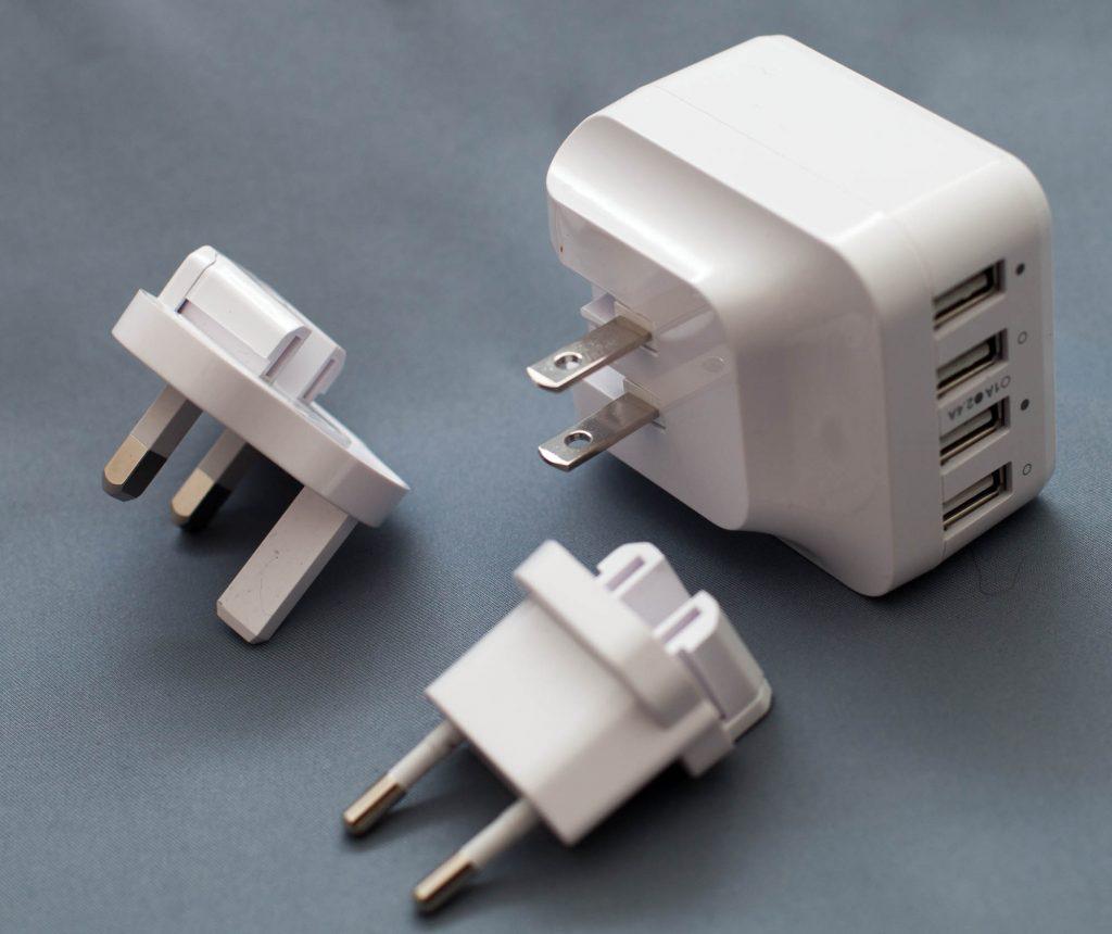 Foto eines 4-fach USB Ladegeräts mit Adaptern für die USA (eingebaut), für Europa und für Großbritannien.