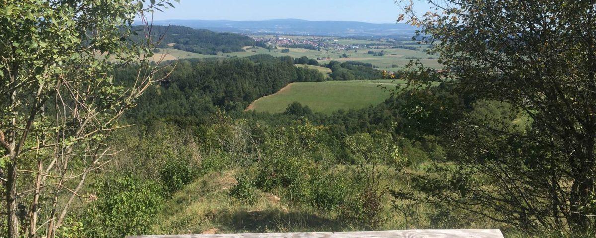Blick von der Neubürg über eine Bank mit dem Logo des fränkischen Gebirgswegs ins Tal